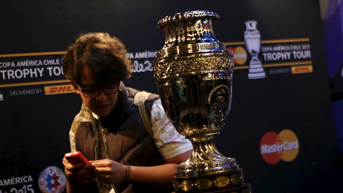 Man walks past the trophy of the Copa America soccer tournament during a ceremony for Copa America Chile 2015 Trophy Tour at the Papalote children's museum in Mexico City