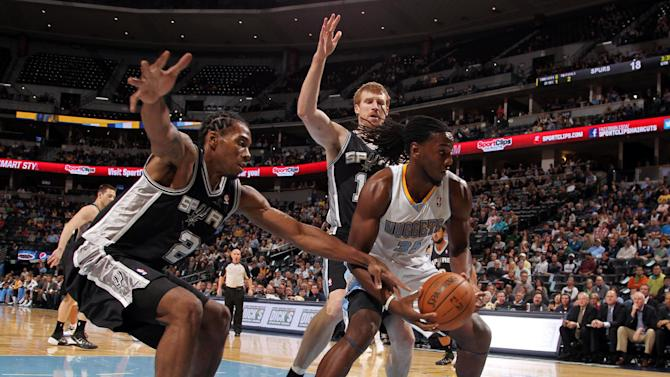 Denver Nuggets forward Kenneth Faried, front right, is trapped with the ball under the net by San Antonio Spurs forward Kawhi Leonard, front, left, and forward Matt Bonner, back, in the first quarter of an NBA preseason basketball game in Denver on Monday, Oct. 14, 2013