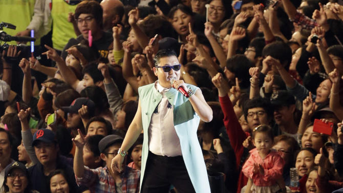 "FILE - South Korean rapper PSY, who sings the popular ""Gangnam Style,"" performs during his concert in front of Seoul City Hall in Seoul, South Korea, in this, Oct. 4, 2012 file photo. YouTube says in a posting on its Trends blog that ""Gangnam Style"" had been viewed 805 million times as of Saturday afternoon, Nov. 24, 2012 surpassing Justin Bieber's ""Baby,"" which has had 803 million views to become YouTube's most viewed video of all time.. (AP Photo/Lee Jin-man, File)"