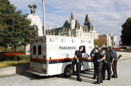 Police officers and ambulance workers gather alongside the Canadian War Memorial following a shooting incident in Ottawa