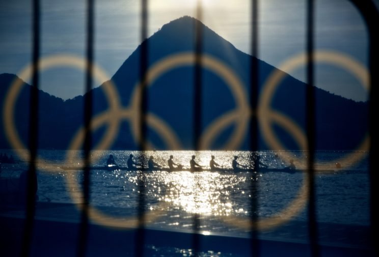 Rowers are seen through a screen decorated with the Olympic rings as they practice at the rowing venue in Lagoa at the 2016 Summer Olympics in Rio de Janeiro, Brazil, Aug. 7, 2016. (Photo: David Goldman/AP)