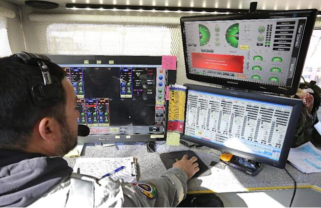 In this March 25, 2014 photo, a technician inside a trailer monitors and directs the pressure and mix of water, sand and chemicals pumped during a hydraulic fracturing operation at an Encana Corp. wel