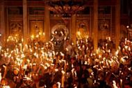 Christian Orthodox worshippers hold up candles lit from the 'Holy Fire' as thousands gather in the Church of the Holy Sepulchre in Jerusalem's old city on the eve of the Orthodox Easter