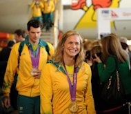 Australian Olympic swimmer Libby Trickett (C) disembarks from a Qantas 747-400 plane inside a hangar at the Sydney Domestic Airport on August 15, 2012. Australia's Olympic athletes were welcomed home by a big crowd with Australian Prime Minister Julia Gillard defending their achievements despite a poor medal haul