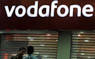 India says it will change a law to allow it to tax foreign firms for acquisitions of assets in the country after it lost a $2.2 bn fight with British mobile phone giant Vodafone