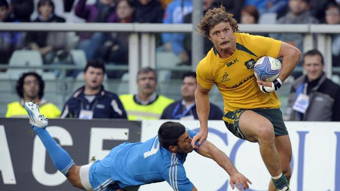 Australia's Nick Cummins evades a tackle from Italy's Edoardo Gori during their Six Nations rugby union match at the Olympic stadium in Turin
