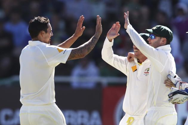 Australia's Mitchell Johnson, Dave Warner and Michael Clarke celebrate the wicket of Faf du Plessis during the third day of the third cricket test match against South Africa at Newlands Stadium in