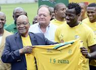 South Africa's President Jacob Zuma (L) receives a team jersey from the South African football team captain Bongani Khumalo (R) at Orlando Stadium in Soweto on January 15, 2013. Khumalo has highlighted the importance of home support in his team's quest to be crowned African champions