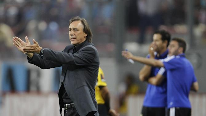 Brazil's Atletico Paranaense coach Miguel Angel applauds his players during a Copa Libertadores soccer match against Peru's Sporting Cristal, in Lima, Peru, Wednesday, Jan. 29, 2014