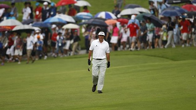 Phil Mickelson of the U.S. walks down the eighth fairway as spectators carrying umbrellas follow in the light drizzle during the rain-delayed second round of the Barclays Singapore Open golf tournament in Sentosa (Reuters)