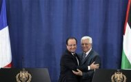 Palestinian President Mahmoud Abbas (R) and his French counterpart Francois Hollande embrace during a joint news conference in the West Bank city of Ramallah November 18, 2013. REUTERS/Ammar Awad