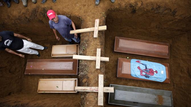 Men stand next to coffins during the funeral for six children who died in a landslide in La Chicharronera