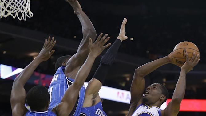 Golden State Warriors' Jordan Crawford, right, shoots against Orlando Magic guard Doron Lamb (1) and forward Tobias Harris (12) during the second half of an NBA basketball game Tuesday, March 18, 2014, in Oakland, Calif