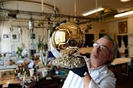 French artisan Michel Garault works on the FIFA Ballon d'Or 2012 ('Golden Ball'), at the Mellerio jewelery workshops in Paris, on December 6, 2012. The displays at Mellerio jewellers in Paris teem with diamonds and sapphires. But to football fans they pale in comparison with the golden orb on a bed of pyrite crafted by the house for the FIFA Ballon d'Or