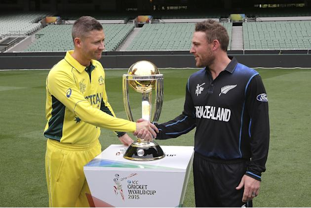 Australia's captain Michael Clarke, left, and New Zealand's captain Brendon McCullum shake hands as they pose for a photo with the Cricket World Cup trophy at the MCG in Melbourne, Australia, Satu