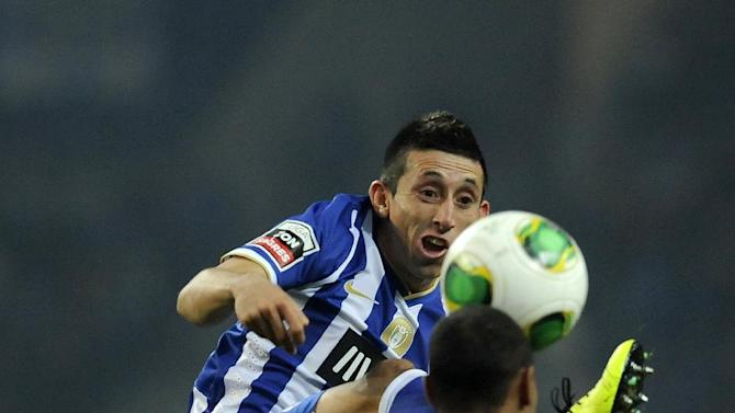 FC Porto's Hector Herrera, from Mexico, rear, vies for a high ball Sporting Braga's Wanderson Baiano, from Brazil, in a Portuguese League soccer match at the Dragao Stadium in Porto, Portugal, Saturday, Dec. 7, 2013