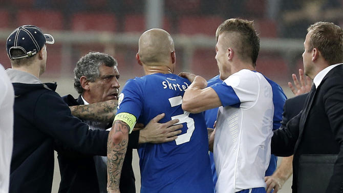 Greece's coach Fernando Santos from Portugal, second left, holds Slovakia's captain Martin Skrtel (3) as he tries to confront  a Greek player after their World Cup Group G qualifying soccer match at the Karaiskaki stadium in the port of Piraeus, near Athens, Friday, Oct. 11, 2013. Greece won 1-0
