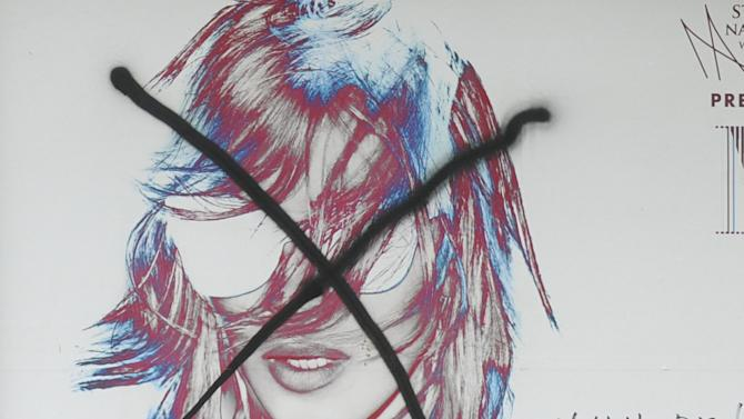 A woman walks past a defaced Madonna concert billboard in Warsaw, Poland, Wednesday, July 18, 2012.  Organizers of the concert have agreed to a request from city officials to start the show with a minute of silence and a brief clip about the 1944 revolt against Nazi rule, the Warsaw Uprising, in a nod to war veterans. Some veterans and young Catholics have voiced anger that the Aug. 1 concert falls on the 68th anniversary of the uprising, a day marked with a somber tone. (AP Photo/Alik Keplicz)