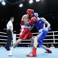 Kaeo Pongprayoon of Thailand (in red) defends against Aleksandar Aleksandrov of Bulgaria (in blue) during the Light Flyweight boxing quarterfinals of the 2012 London Olympic Games at the ExCel Arena in London. Pongprayoon advanced to the semi-finals with a 16-10 points decision