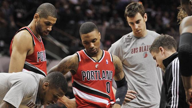 Portland Trail Blazers forward LaMarcus Aldridge (12) is helped by medical staff as teammates watch during the second half of an NBA basketball game against the San Antonio Spurs on Wednesday, March 12, 2014, in San Antonio. San Antonio won 103-90