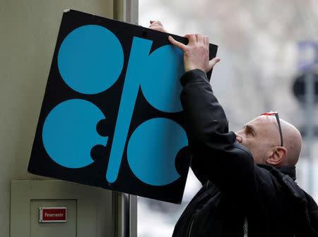 文件图片:在维也纳的欧佩克石油部长会议之前,一名男子在其总部入口旁边的石油输出国组织标志旁边标上了一块标有欧佩克标志的标志。