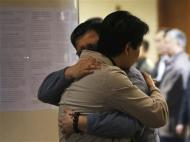 Family members of a passenger onboard the missing Malaysian Airlines flight MH370 hug each other as they wait for news about the missing plane at a hotel in Beijing March 20, 2014. REUTERS/Kim Kyung-Hoon