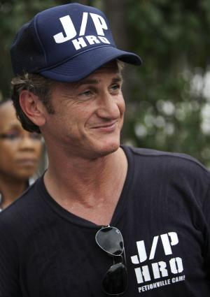 FILE - In this March 14, 2010, U.S. actor Sean Penn smiles while watching the motorcade of U.N. Secretary-General Ban Ki-moon departing from the makeshift camp for earthquake survivors set up in the Petionville Golf Club in Port-au-Prince, Haiti. An aid group run by Hollywood actor Sean Penn announced Tuesday, March 12, 2013 it is receiving $8.75 million from the World Bank to help move Haitians off of a golf course where many have been living since the January 2010 earthquake. Penn's J/P Haitian Relief Organization took responsibility for the impromptu settlement a couple of months after the quake, which destroyed thousands of buildings. (AP Photo/Andres Leighton, File)