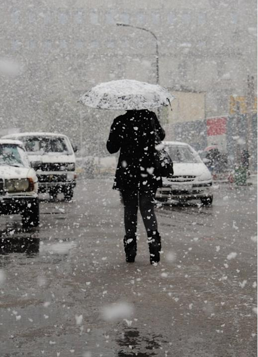 A Syrian woman walks in central Damascus during snow fall on January 9, 2013 as a fierce storm whipped the region this week and temperatures dropped dramatically.   AFP PHOTO/ STR