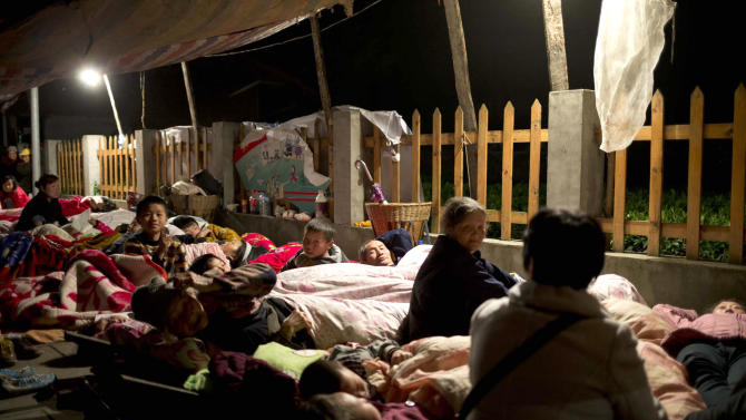 In this photo released by China's Xinhua News Agency, residents of Yuxi Village in the quake hit Baosheng Township spend their night in temporary tents in Lushan County, Ya'an City, southwest China's Sichuan Province, Saturday, April 20, 2013. Residents huddled outdoors in the town near the epicenter of a powerful earthquake that struck the steep hills of China's southwestern Sichuan province Saturday morning, leaving at least 160 people dead and more than 6,700 injured.  (AP Photo/Xinhua, Fei Maohua) NO SALES