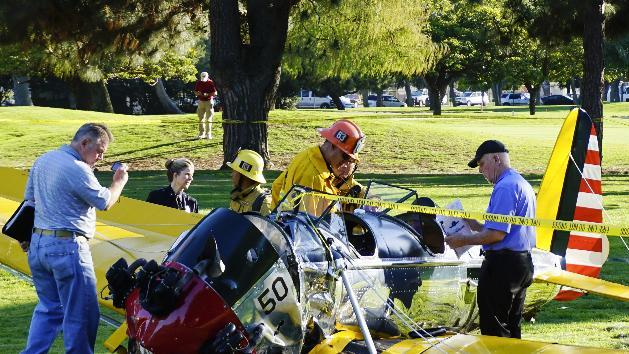 Officials work on the scene of a vintage plane that Harrison Ford crash-landed on the Penmar Golf Course in the Venice area of Los Angeles (AP)
