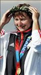 German Birgit Fischer adjusts her wreath after receiving her gold medal with teammates Nollen Maike, Katrin Wagner and Carolin Leonhardt (not pictured) during the medals ceremony for the Women's K4 500m final for the Athens 2004 Olympic Games at the Schinias Rowing and Canoeing Center, outside Athens, 27 August 2004. AFP PHOTO / MLADEN ANTONOV