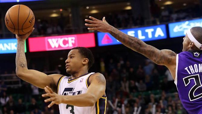 Utah Jazz's Trey Burke (3) takes a shot as Sacramento Kings' Isaiah Thomas, right, defends in the second half of an NBA basketball game on Saturday, Dec. 7, 2013, in Salt Lake City. The Kings went on to win 112-102 in overtime