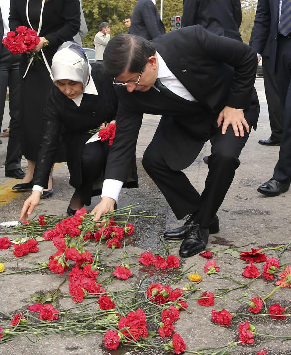 Turkish Prime Minister Ahmet Davutoglu and his wife Sare Davutoglu leave carnations at the site of an explosion in Ankara, Turkey, Tuesday, Oct. 13, 2015. Authorities in Istanbul banned a protest rall