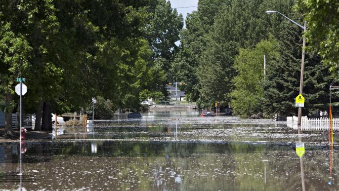 Cars are partially-submerged as water recedes from a street in High River, Alberta, Canada on Saturday, June 22, 2013 after the Highwood River overflowed its banks. (AP Photo/The Canadian Press, Jordan Verlage)