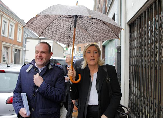 French far-right party leader Marine Le Pen, right, and her National's suppleant Steve Briois campaign for the municipal elections in Henin-Beaumont northern France, Friday, March 21, 2014. Marine