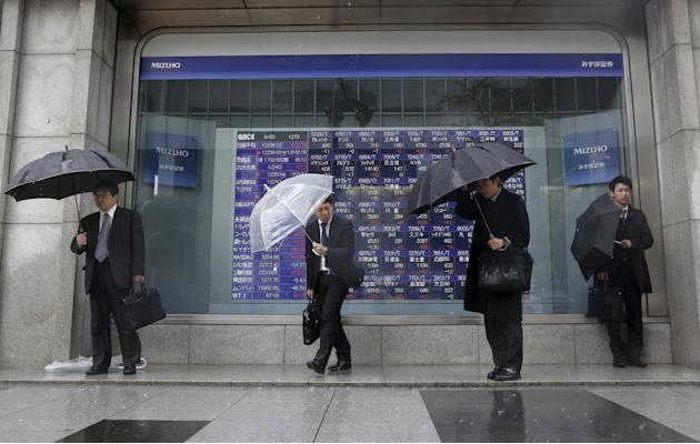 File photo of pedestrians holding umbrellas standing in front of a stock index board showing various stock prices outside a brokerage in Tokyo