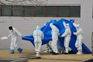 Japan Self-Defence Force officers in radiation protection suits hold a blue sheet over patients who were exposed to high levels of radiation at the the Fukushima nuclear power plant as they are transferred to the Fukushima Medical University hospital on March 25. Radiation levels have surged in seawater near a tsunami-stricken nuclear power station in Japan, officials said Saturday