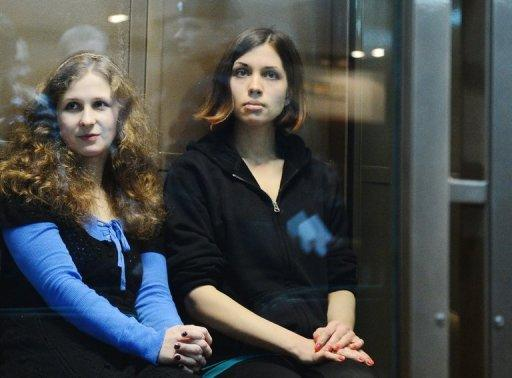"""The two jailed members of the all-girl punk band """"Pussy Riot,"""" Maria Alyokhina (L) and Nadezhda Tolokonnikova (R), sit in a glass-walled cage in a court in Moscow in October 2012. Alyokhina and Tolokonnikova have fired their high-profile legal team and hired the lawyer who helped free their bandmate, the husband of one of the women told AFP on Monday."""