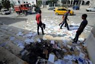 Tunisians pass by the remains of charred documents outside the office of Tunisia's ruling Islamist party Ennahda that was torched by protesters on October 24, 2013 in Kef
