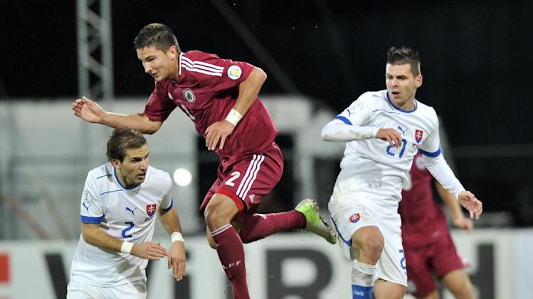 Latvia's Vitalijs Maksimenko, centre, vies for the ball with Slovakia's Peter Pekarik, left, and Michal Duris during their World Cup 2014 Group G qualification match in Riga, Latvia, on Tuesday. October 15, 2013