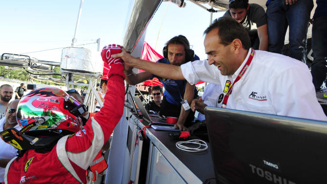 AF Corse Ferrari driver Gianmaria Bruni, left, of Italy, celebrates with his team after taking the GT class pole position for the American Le Mans Series' Petit Le Mans auto race at Road Atlanta, Friday, Sept. 30, 2011, in Braselton, Ga. (AP Photo/Rainier Ehrhardt)