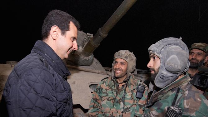 A picture released by the Syrian Arab News Agency shows Syrian President Bashar al-Assad (L) talking with troops during a reported visit to the eastern Damascus district of Jobar on December 31, 2014