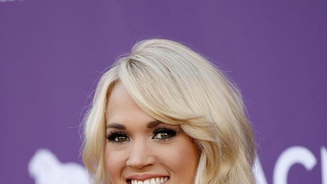 FILE - In this April 1, 2012 photo, singer Carrie Underwood arrives at the 47th Annual Academy of Country Music Awards in Las Vegas. Underwood was nominated Monday, April 23, 2012 for five CMT Music Awards. The show will air live June 6 from Nashvhille, Tenn.(AP Photo/Isaac Brekken, file)