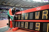 Kenya's David Lekuta Rudisha poses next to the record board after winning the men's 800 final at the athletics event during the London 2012 Olympic Games on August 9, 2012 in London. Rudisha clocked a new world record of 1min 40.91sec. AFP PHOTO / FRANCK FIFE