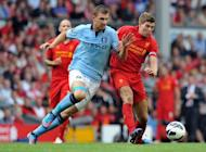 Manchester City's Bosnian forward Edin Dzeko (L) and Liverpool's English midfielder Steven Gerrard compete during an English Premier League football match between Liverpool and Manchester City at Anfield in Liverpool, northwest England. The match ended in a 2-2 draw