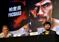 Manny Pacquiao (right) and trainer Freddie Roach at a press conference in Beijing on Tuesday. Philippine boxing hero Pacquiao has no immediate plans to run for president, his chief aide said Tuesday, following a fierce political backlash to comments he wanted to lead his country