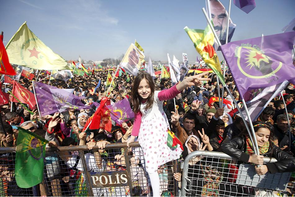 Kurdish girl gestures while others wave Kurdish flags during a gathering celebrating Newroz, which marks the arrival of spring and the new year, in Istanbul