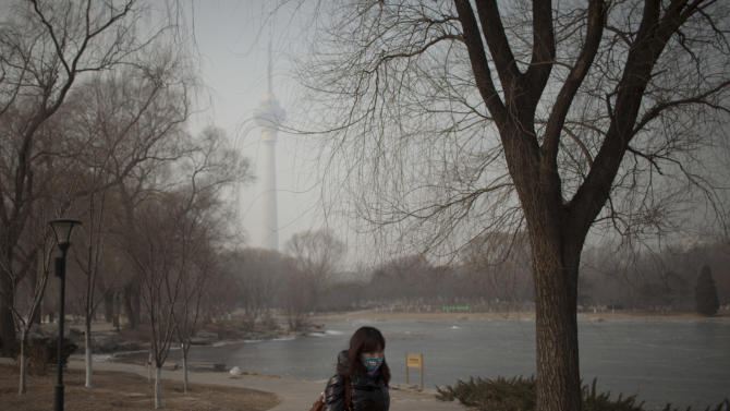 A woman wears a mask while walking in a park near the China Central Television Tower, background, on a hazy day in Beijing, China, Monday, Jan. 14, 2013. Beijing schools kept children indoors and hospitals saw a spike in respiratory cases Monday following a weekend of off-the charts pollution in China's smoggy capital, the worst since the government began being more open about air-quality data. (AP Photo/Alexander F. Yuan)