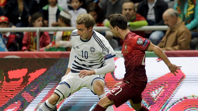 Portugal's Cedric fights for the ball with Denmark's Eriksen during their Euro 2016 qualifying soccer match at Municipal Stadium in Braga