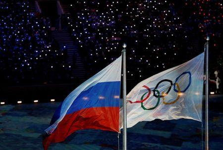 Russian national flag flutters next to Olympics flag during closing ceremony for 2014 Sochi Winter Olympics